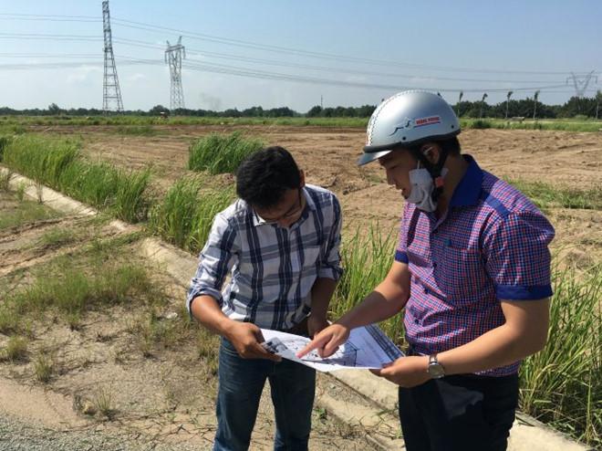 2 người đàn ông đang đứng xem 1 tấm bản đồ, xung quanh là khu đất rộng bỏ hoang