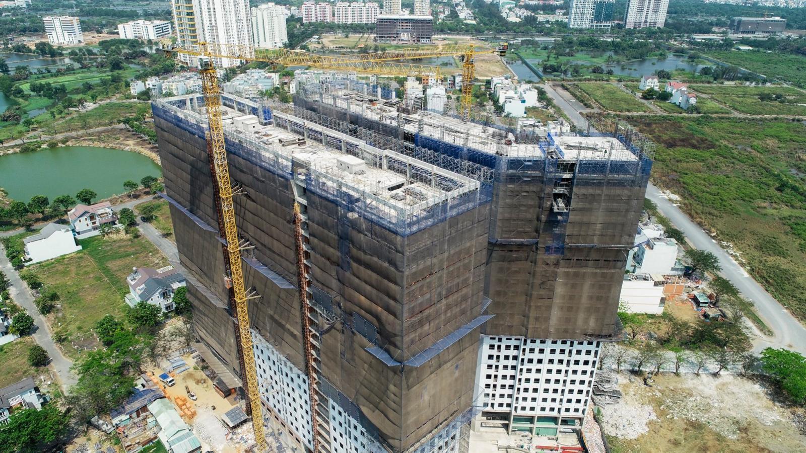 Tòa chung cư cao tầng đang xây dựng, bọc lưới bảo vệ màu xám bên ngoài.