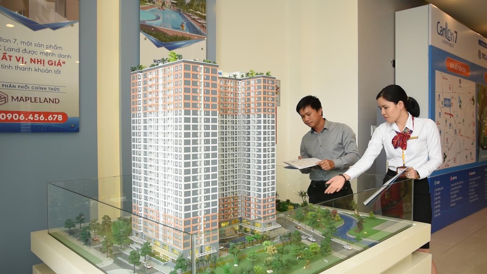 Nhân viên môi giới bất động sản nữ giới thiệu một khách hàng nam sa bàn một dự án căn hộ chung cư.