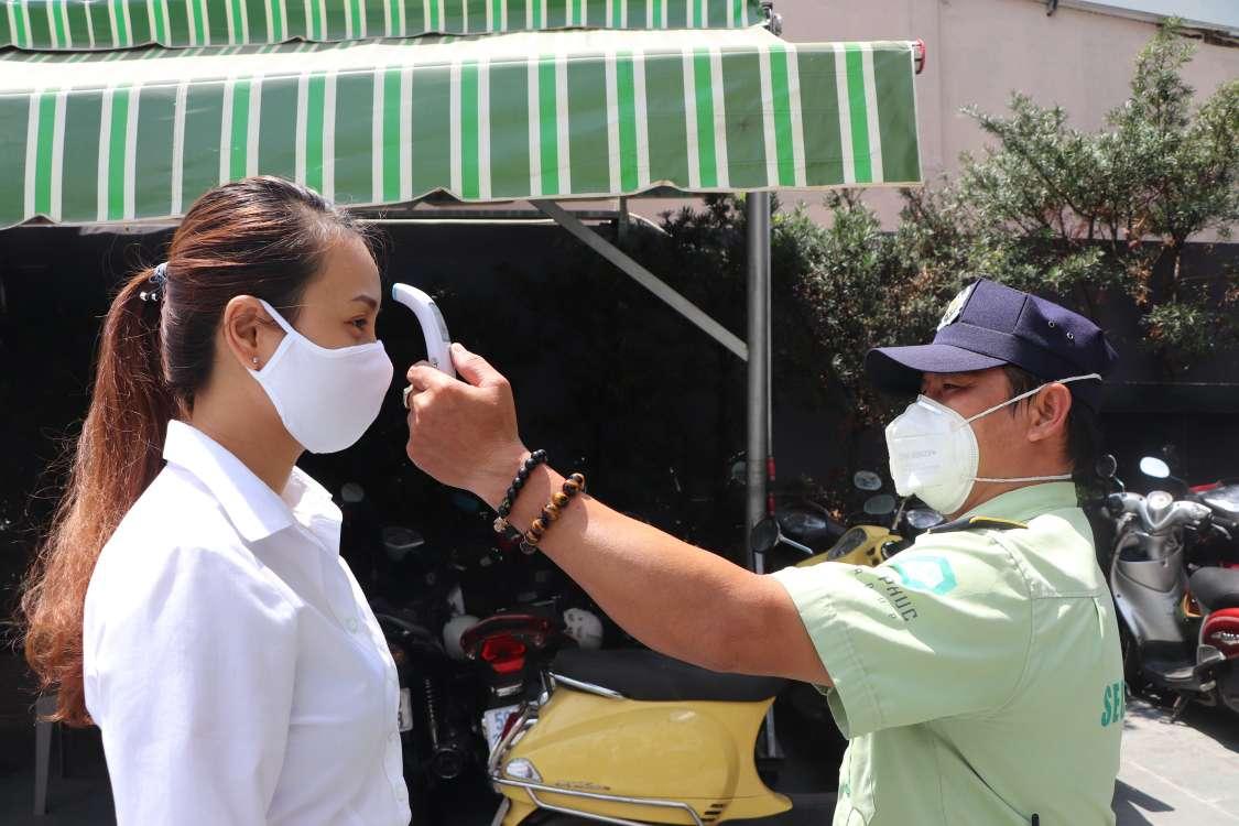 Người đàn ông đeo khẩu trang, đội mũ đang đo nhiệt độ cho người phụ nữ đeo khẩu trang