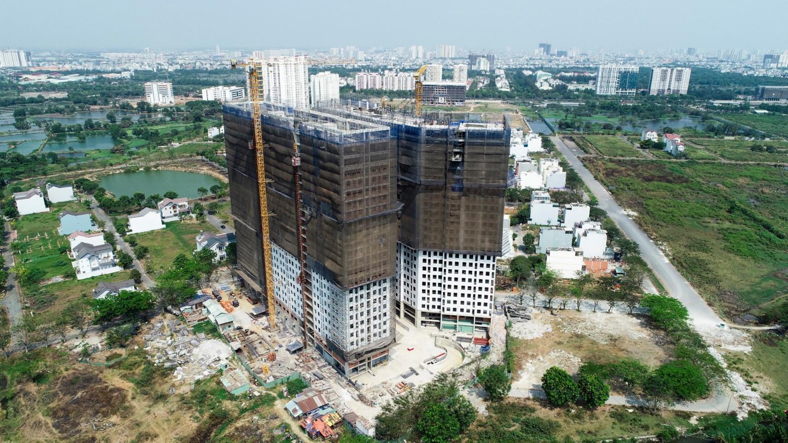 Ảnh chụp trên cao hai tòa chung cư đang xây dựng, bọc lưới đen bên ngoài, xung quanh là khu dân cư, ao, hồ.