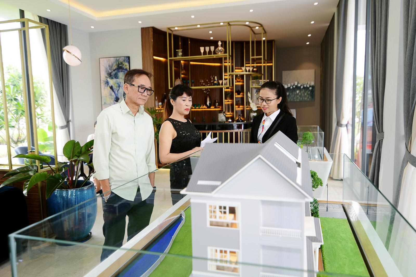 Nhân viên môi giới và hai nhà đầu tư bất động sản đang xem sa bàn một căn biệt thự.