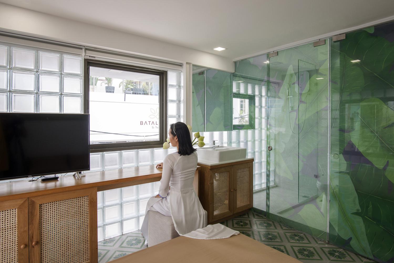 cô gái mặc áo dài trắng ngồi cạnh cửa sổ