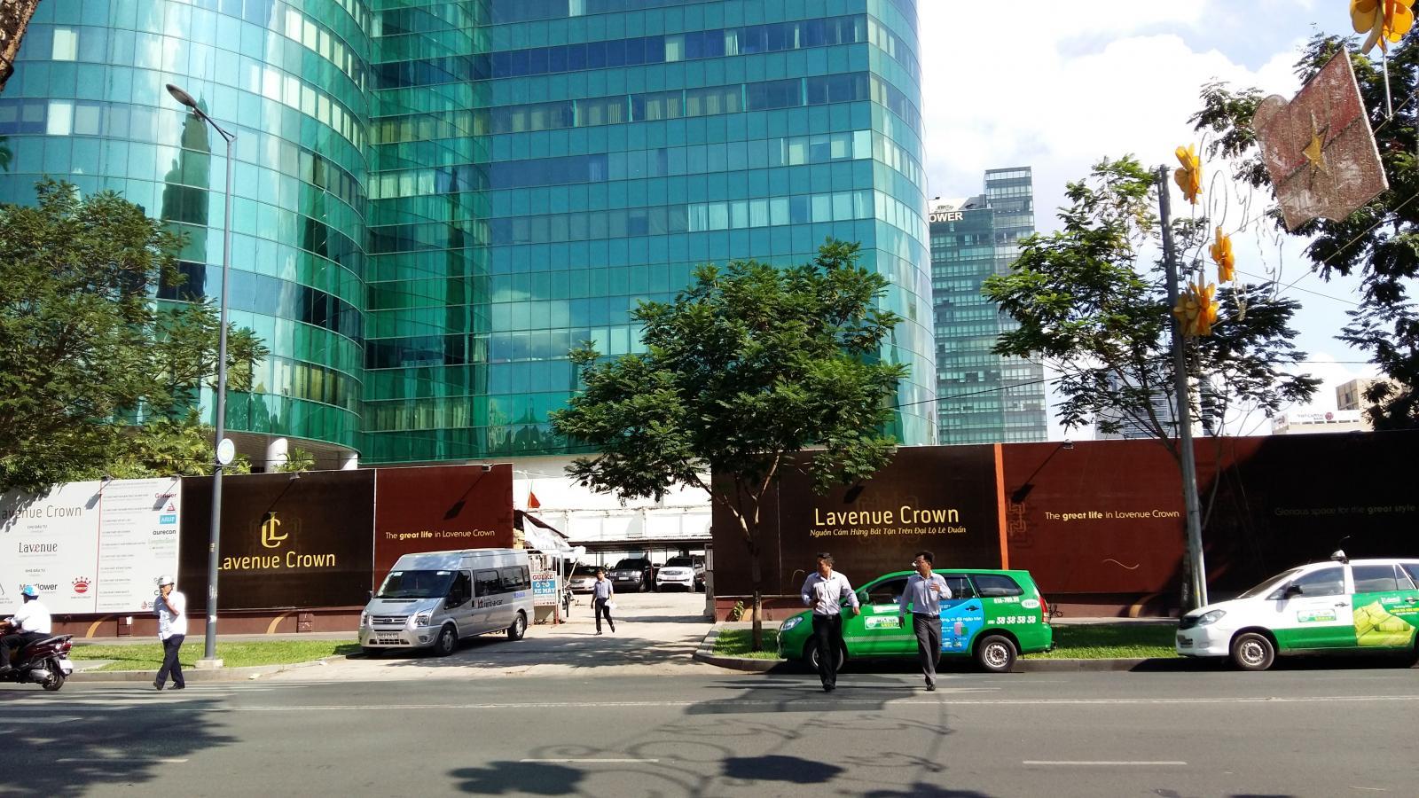 Bên dưới một tòa nhà văn phòng ốp kính, cổng vào, người đi lại, xe ô tô.  Đầu tư bất động sản sẽ chậm lại trong nửa đầu năm 2020 20200323100636 355a