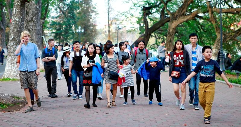 Đoàn du khách đi bộ trên con đường lát gạch quanh hồ Gươm, Hà Nội.