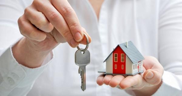 một bàn tay cầm chìa khóa, một bàn tay cầm mô hình ngôi nhà