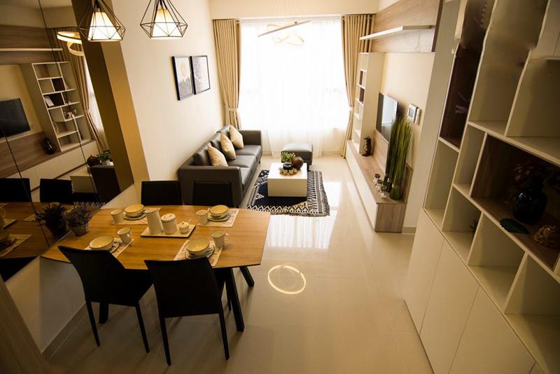 Một góc căn hộ chung cư với bộ bàn ăn kê cạnh bộ ghế sofa phòng khách