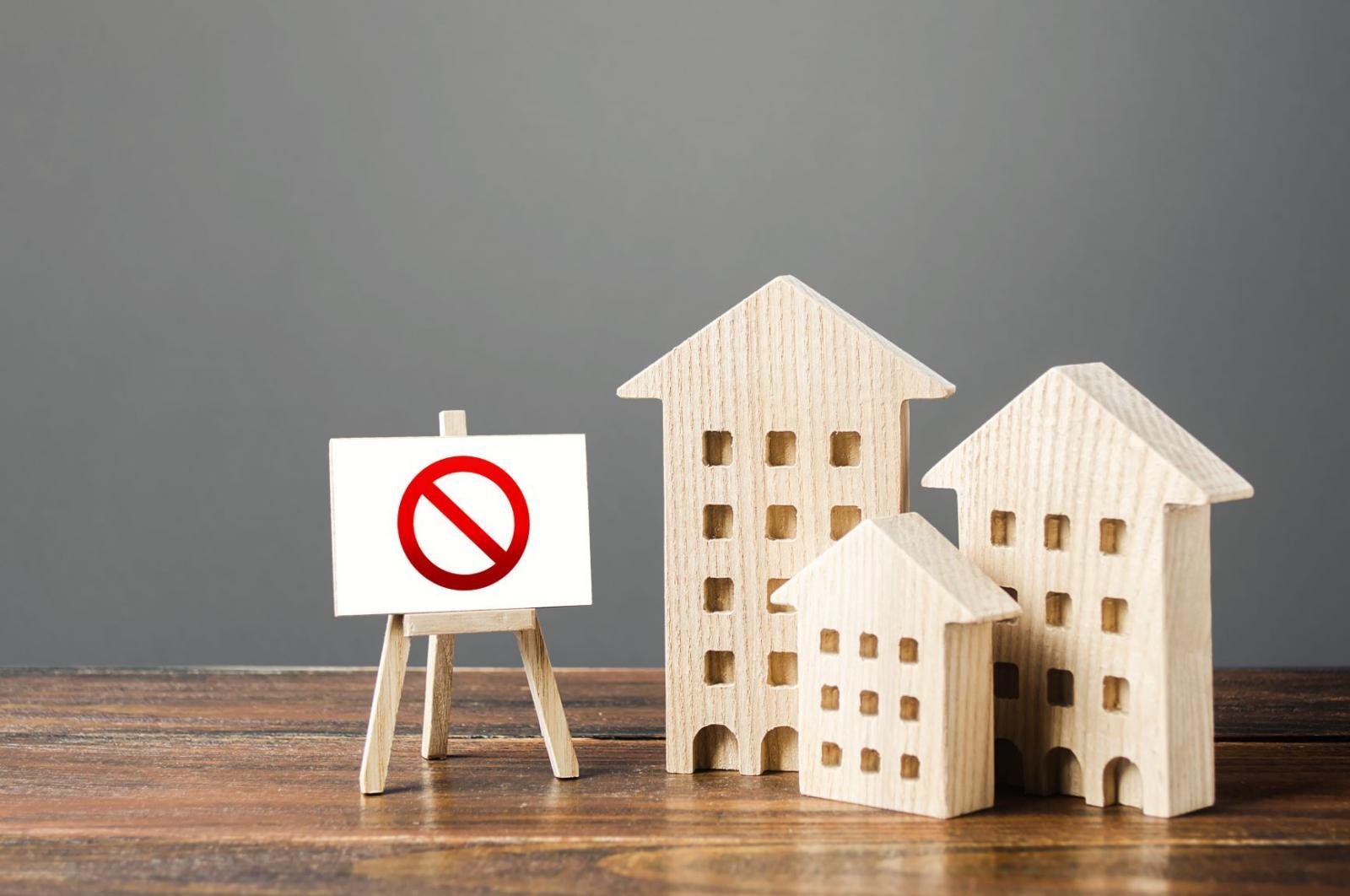 Ba ngôi nhà gỗ mô hình đặt cạnh biển báo ngừng giao dịch màu đỏ.