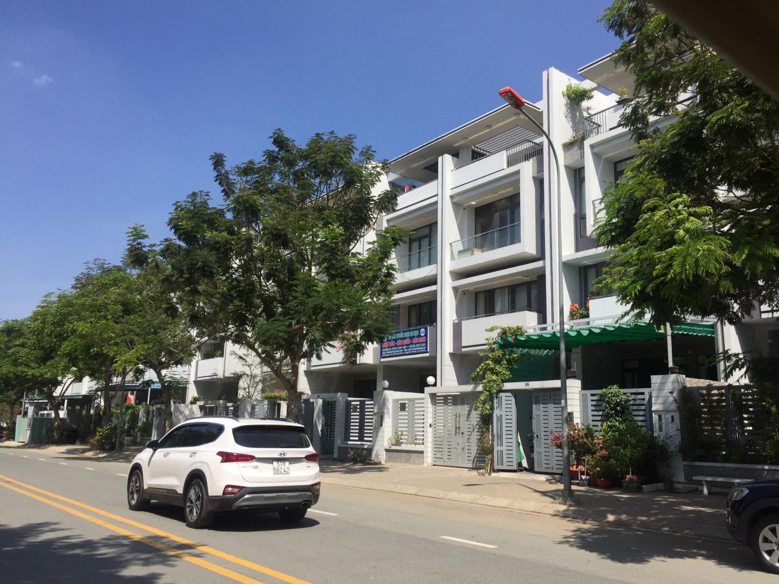 Dãy nhà phố liên kế trong một khu đô thị nằm cạnh đường lớn, ô tô màu trắng, hàng cây xanh.  Phải mất từ 1 đến 2 quý để thị trường bất động sản phục hồi sau dịch 20200417082345 1487
