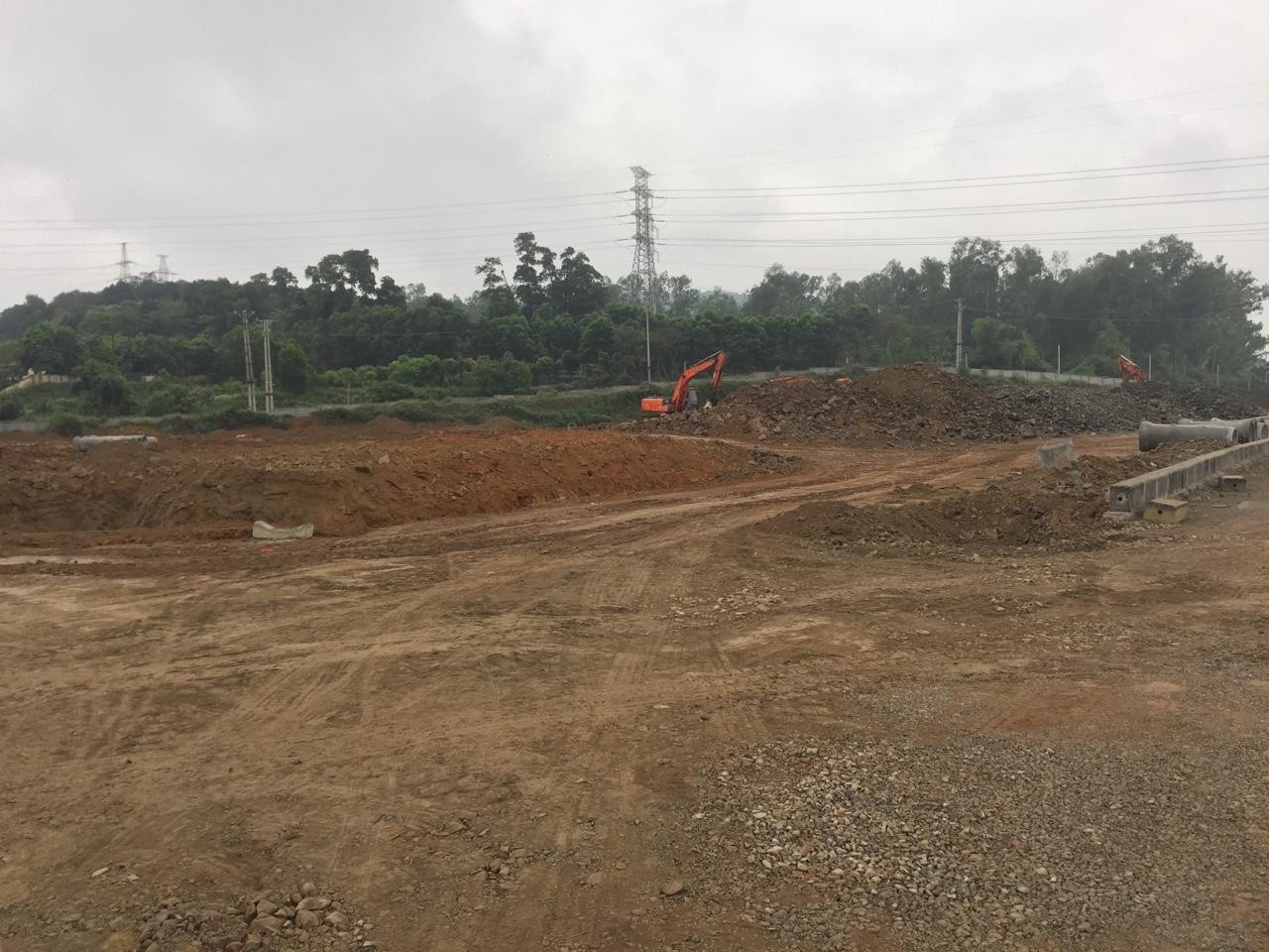 Một dự án đất nền tỉnh lẻ đang san lấp mặt bằng, máy xúc đất đang làm việc.