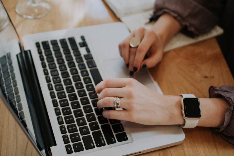 Một người ngồi trên bàn làm việc tại nhà đang gõ phím trên laptop,