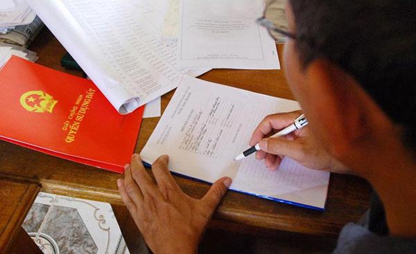 1 chiếc bàn với nhiều giấy tờ, 1 người đàn ông đang ngồi viết