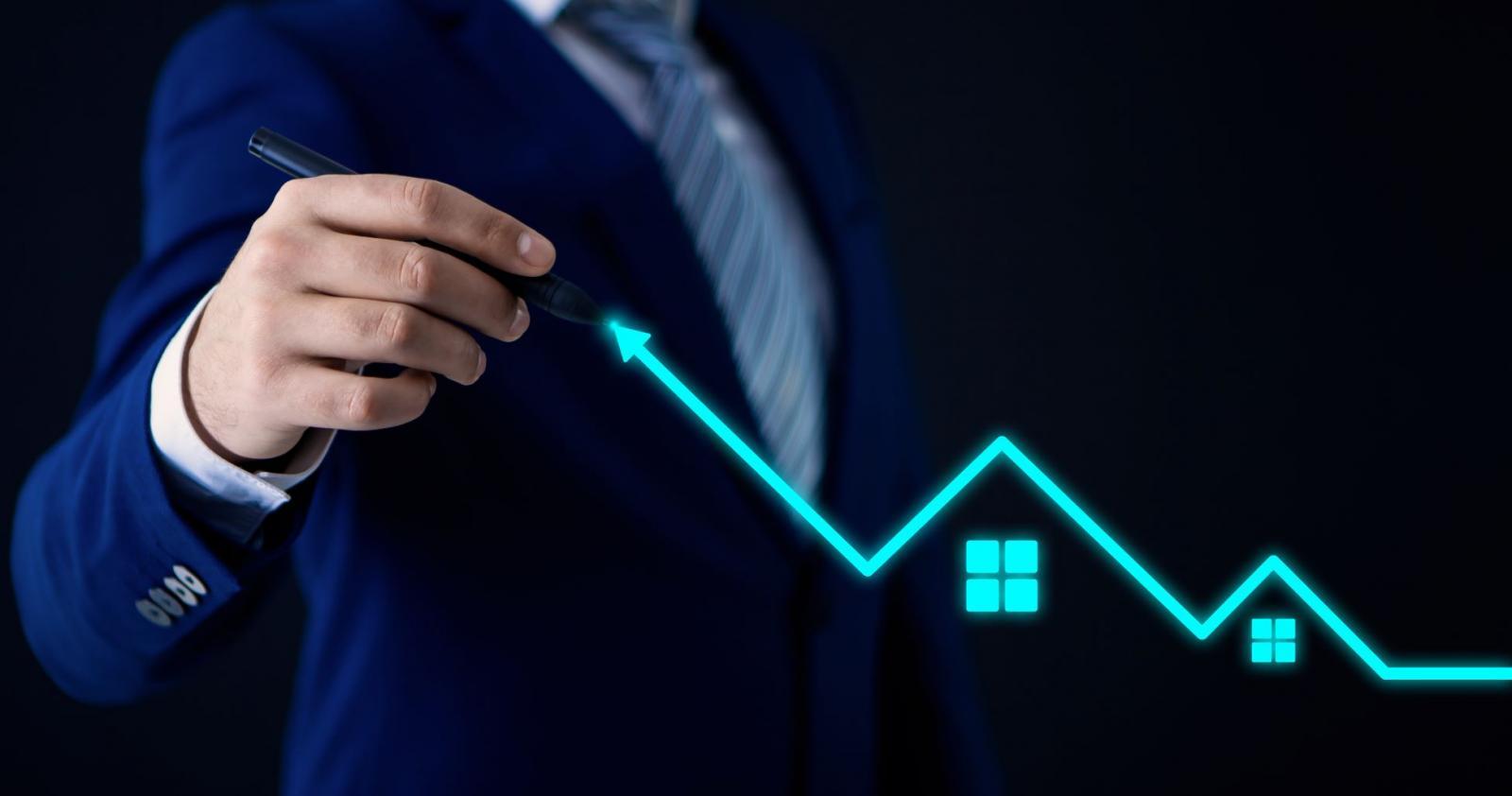 Người đàn ông mặc vest xanh tay cầm bút vẽ một đường zic zắc màu xanh có hình ngôi nhà.