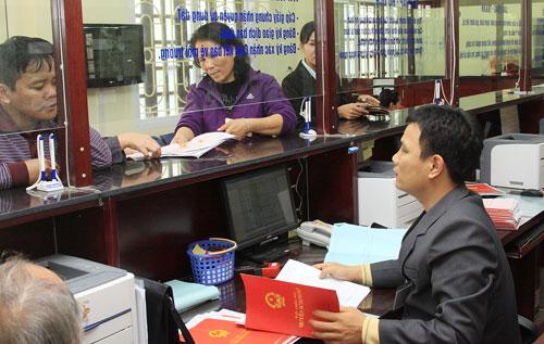 2 khách hàng đang đứng đợi làm thủ tục giấy tờ, một nhân viên ngồi trong quầy giao dịch đang cầm sổ đỏ