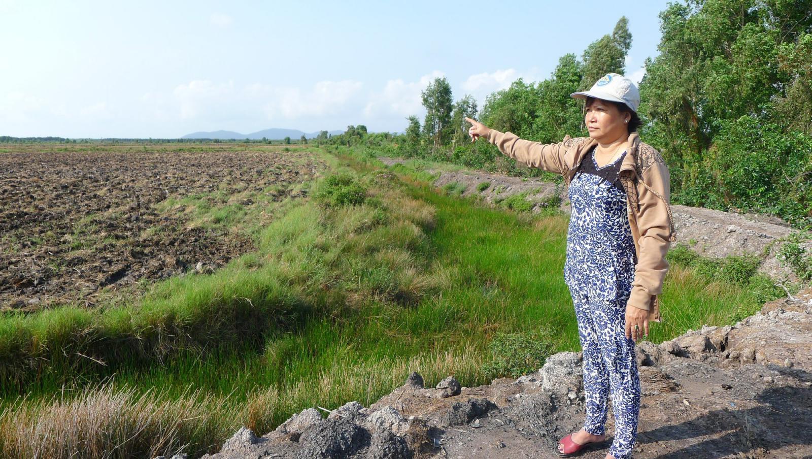 một người phụ nữ đứng chỉ tay ra khu đất trống