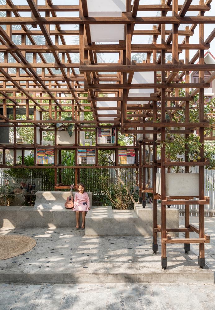 đứa trẻ ngồi cạnh cây đàn trong thư viện bằng gỗ
