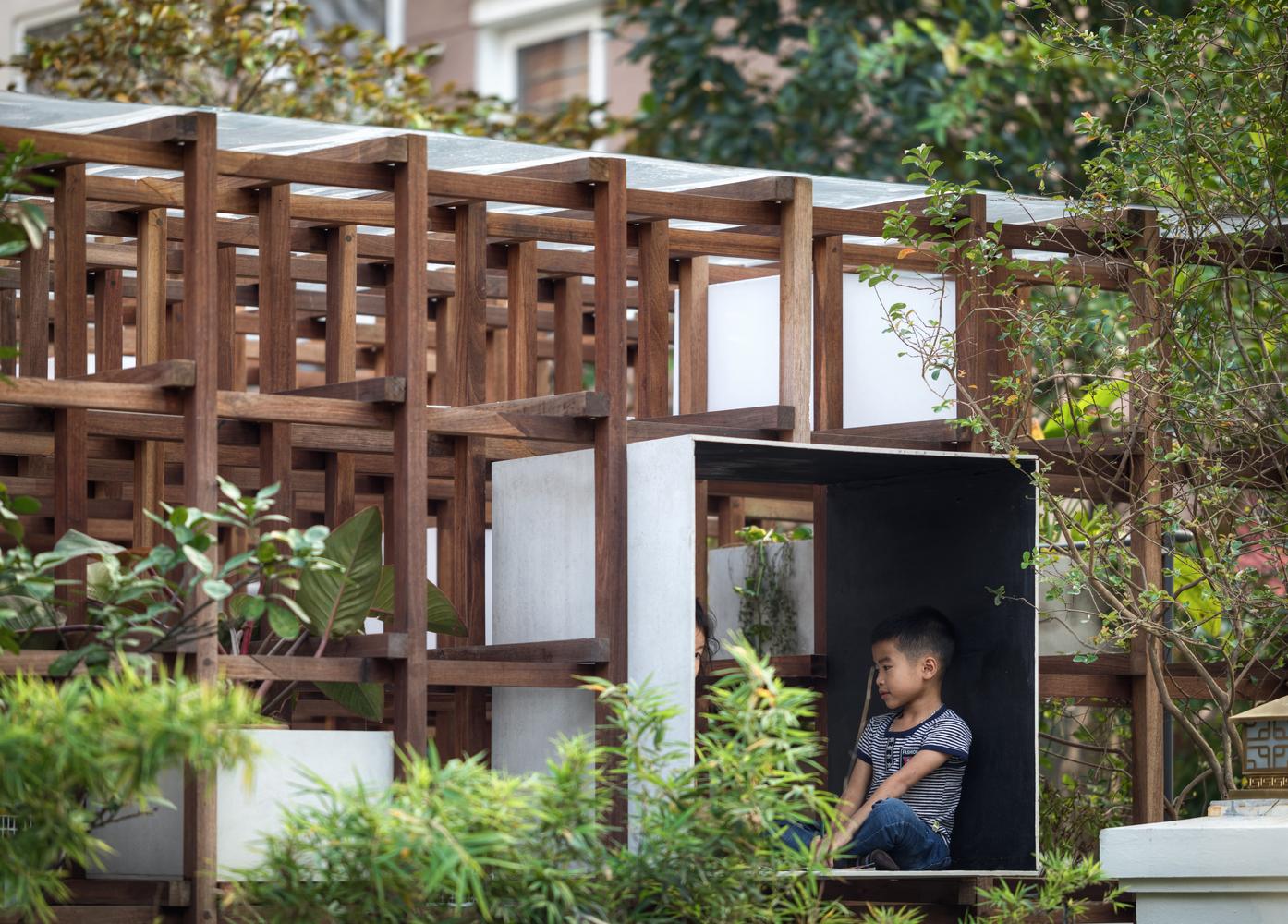 bé trai ngồi trong thư viện bằng gỗ