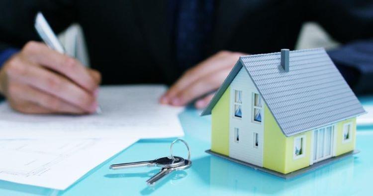Mô hình ngôi nhà và bàn tay cầm bút ký vào một tờ giấy