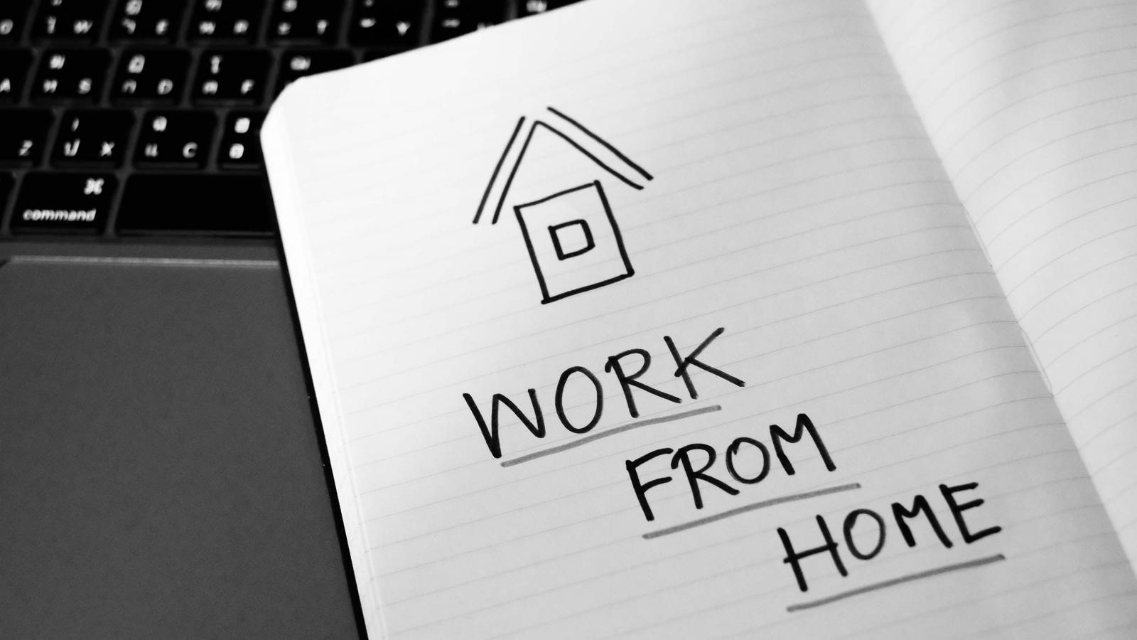 """Quyển vở đặt trên bàn phím máy tính bên trên ghi dòng chữ """"Work From Home"""" và hình ngôi nhà màu đen."""