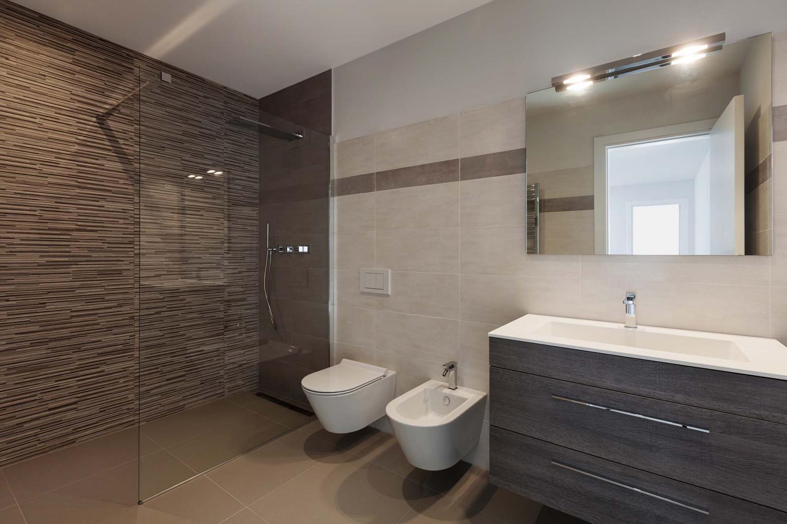 Nhà vệ sinh màu trắng xen kẽ mảng tường nâu, gương treo tường, vách kính phân riêng phòng tắm.