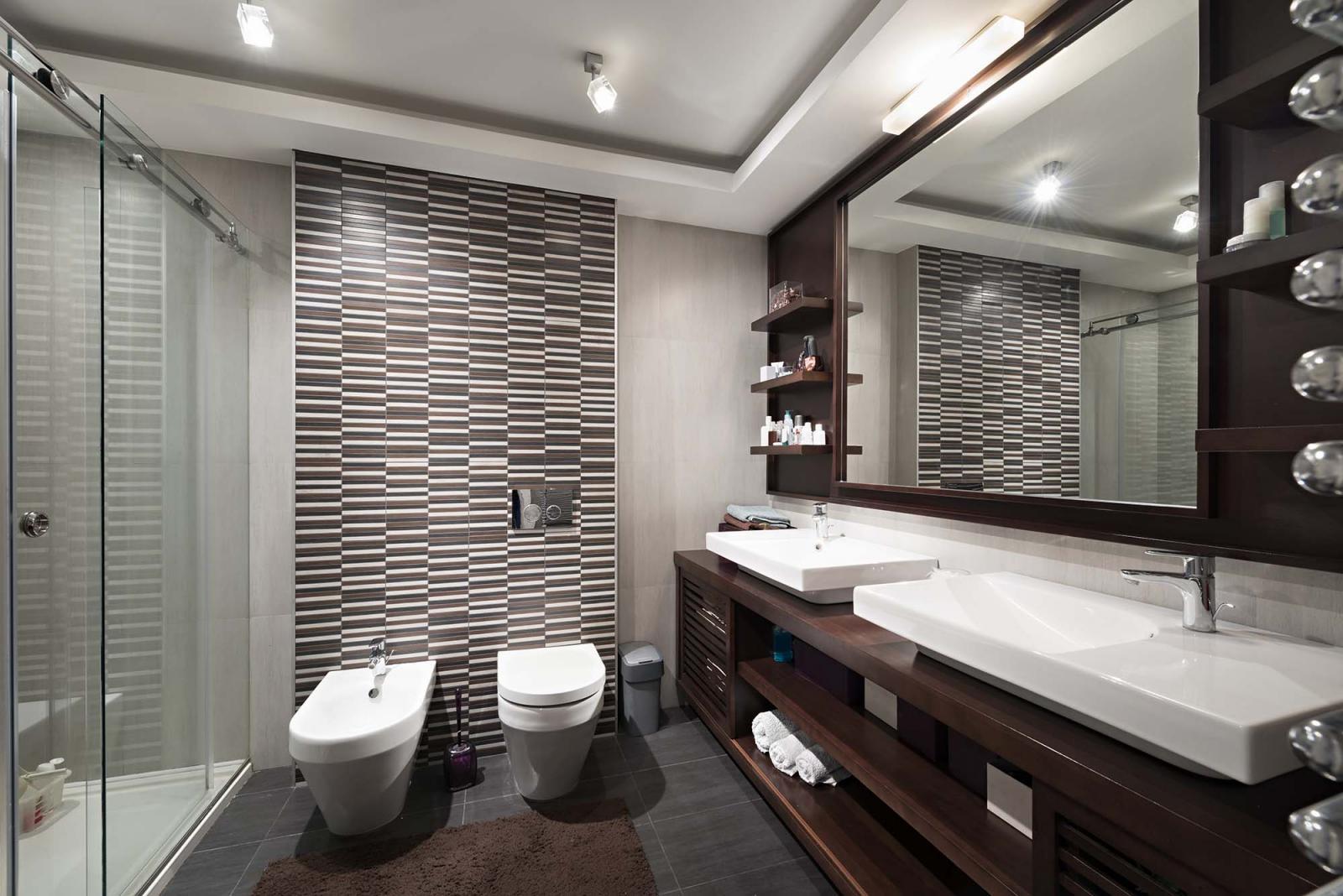 Phòng vệ sinh lớn, hai toilet, hai bồn rửa tay, nhiều bóng đèn thắp sáng.
