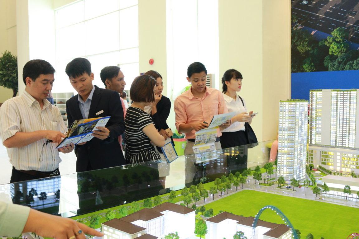 Môi giới bất động sản đang tư vấn khách hàng về dự án, cạnh sa bàn dự chung cư gồm nhiều tòa nhà cao tầng.