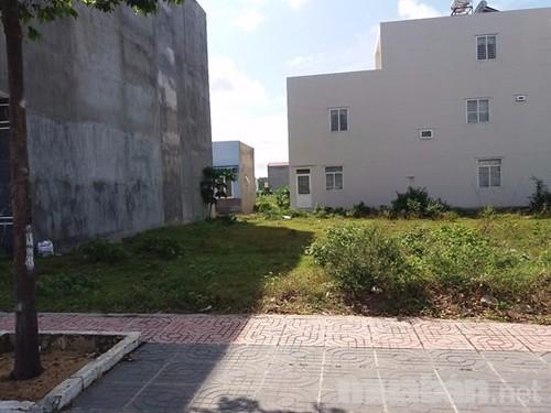 Một mảnh đất trống, bên cạnh là một ngôi nhà cao tầng