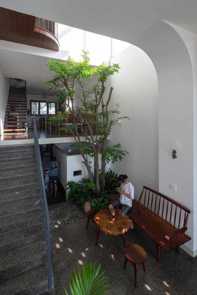 Không gian trong nhà, có cầu thang, bàn ghế, cây cối và người đang sinh hoạt
