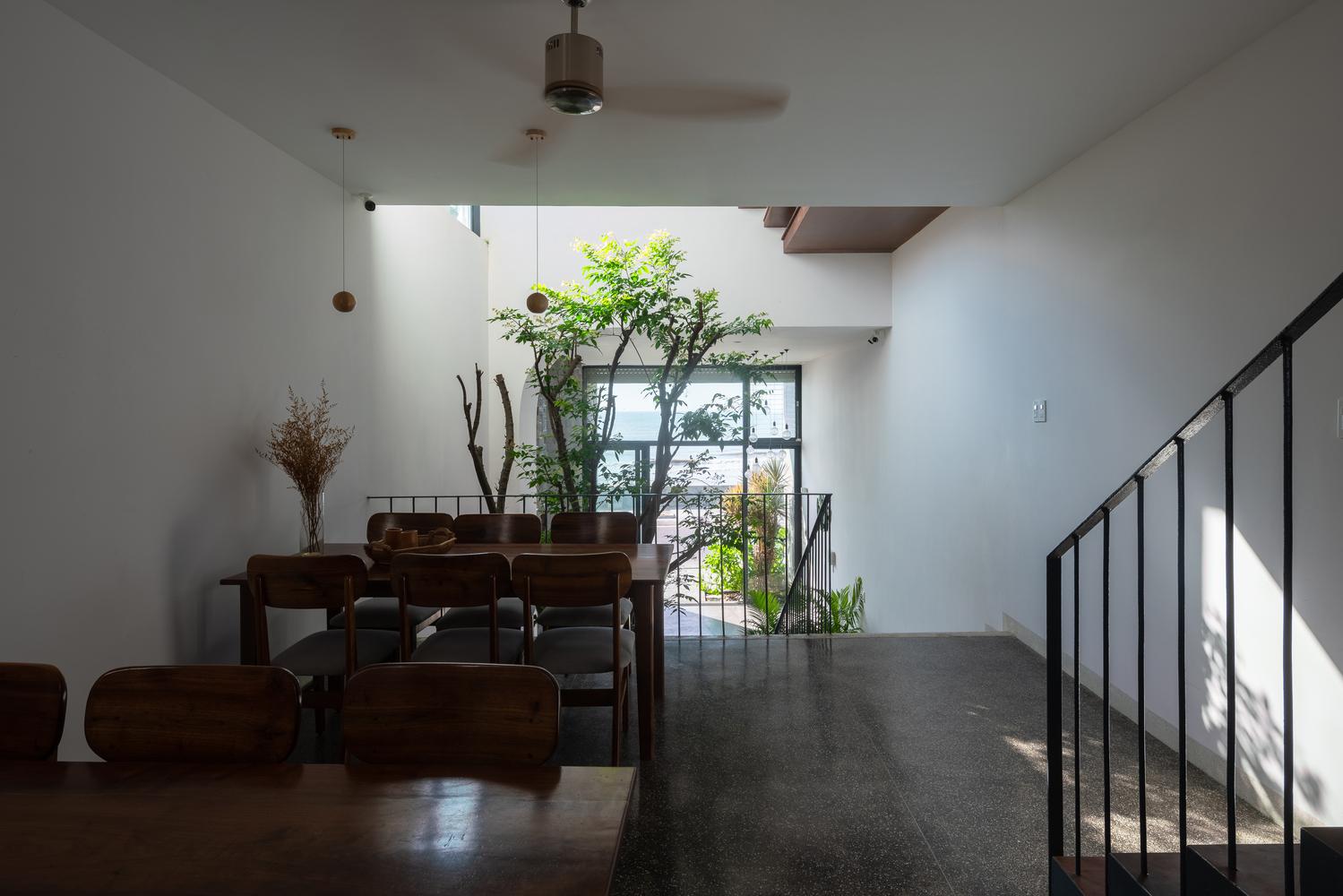 Không gian trong nhà, có bàn ghế và khoảng sáng từ giếng trời