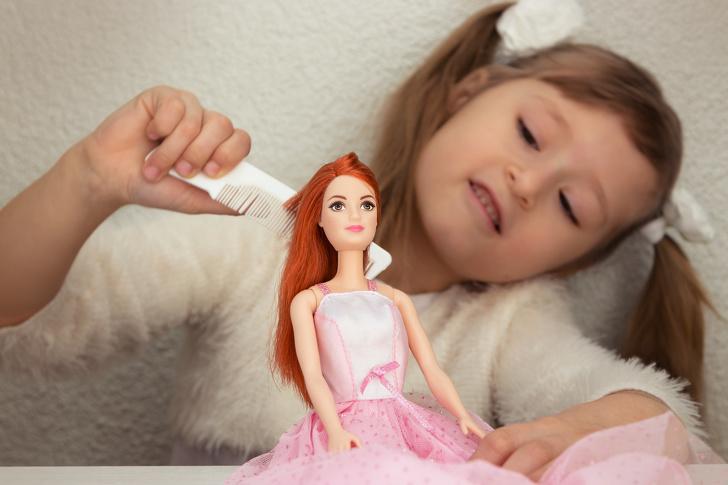 Bé gái chải tóc búp bê