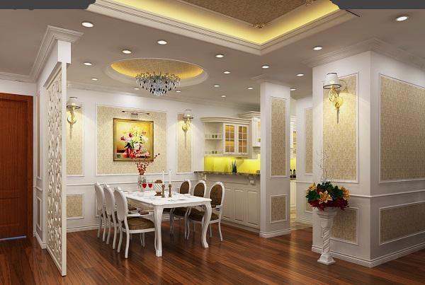 Một góc căn hộ tone trắng với bộ bàn ghế ăn màu trắng kê bên dưới đèn chùm