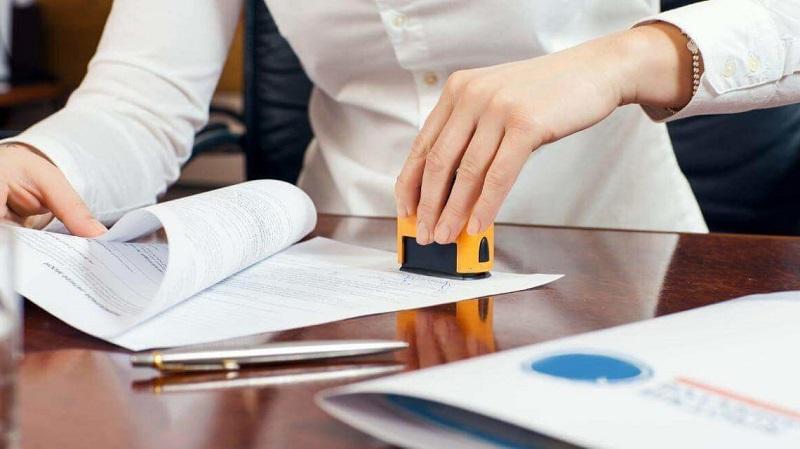 Một người đang cầm con dấu làm thủ tục công chứng hợp đồng đặt cọc mua nhà