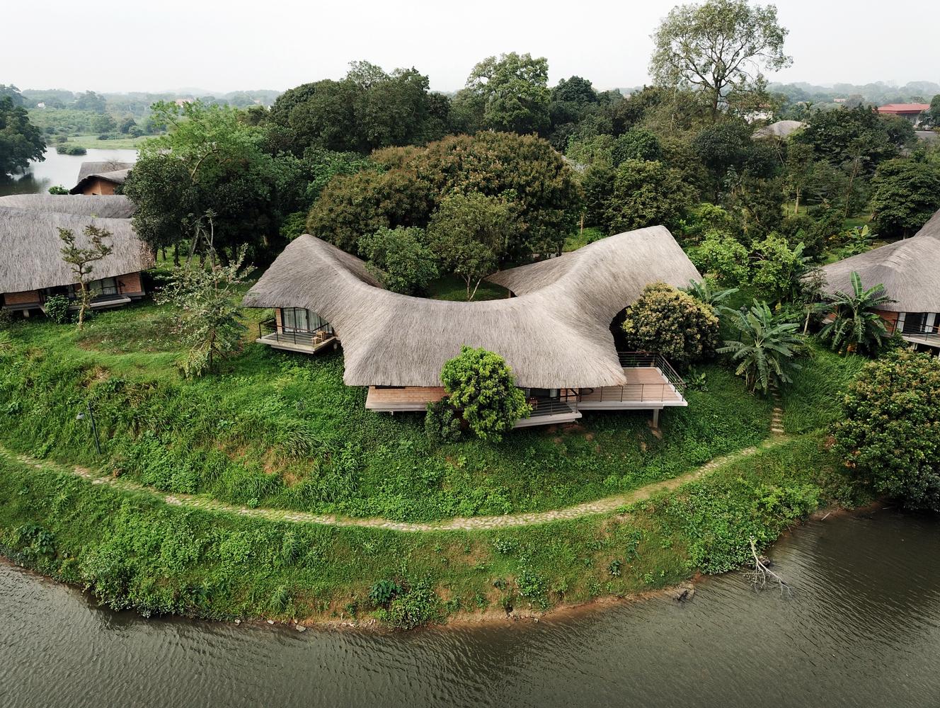 Nhà mái lá cọ bên cạnh hồ nước