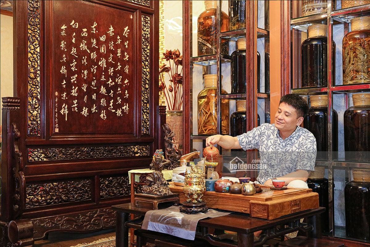 Người đàn ông đang rót trà, xung quanh là phòng khách bày nhiều đồ gỗ mỹ nghệ