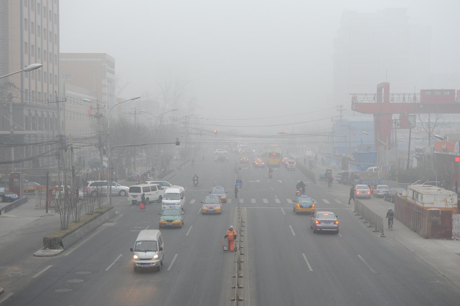 Xe cộ, các tòa nhà cao tầng, cảnh thành phố mờ ảo vì khói bụi ô nhiễm