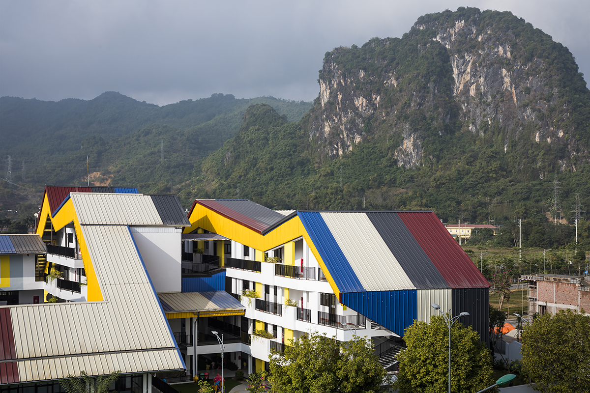 Trường học có mái tôn nhiều màu sắc nổi bật trên nền xanh của núi rừng