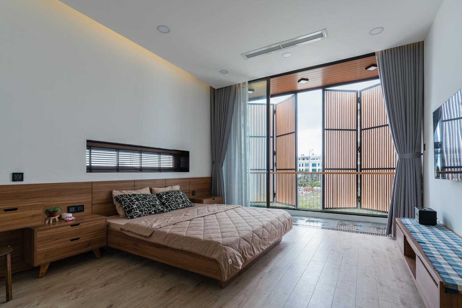 Phòng ngủ có giường, cửa kính sát trần, rèm