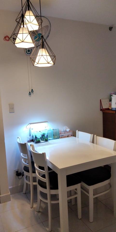 Khu vực phòng ăn với bộ bàn ghế màu trắng, phía trên là đèn trang trí