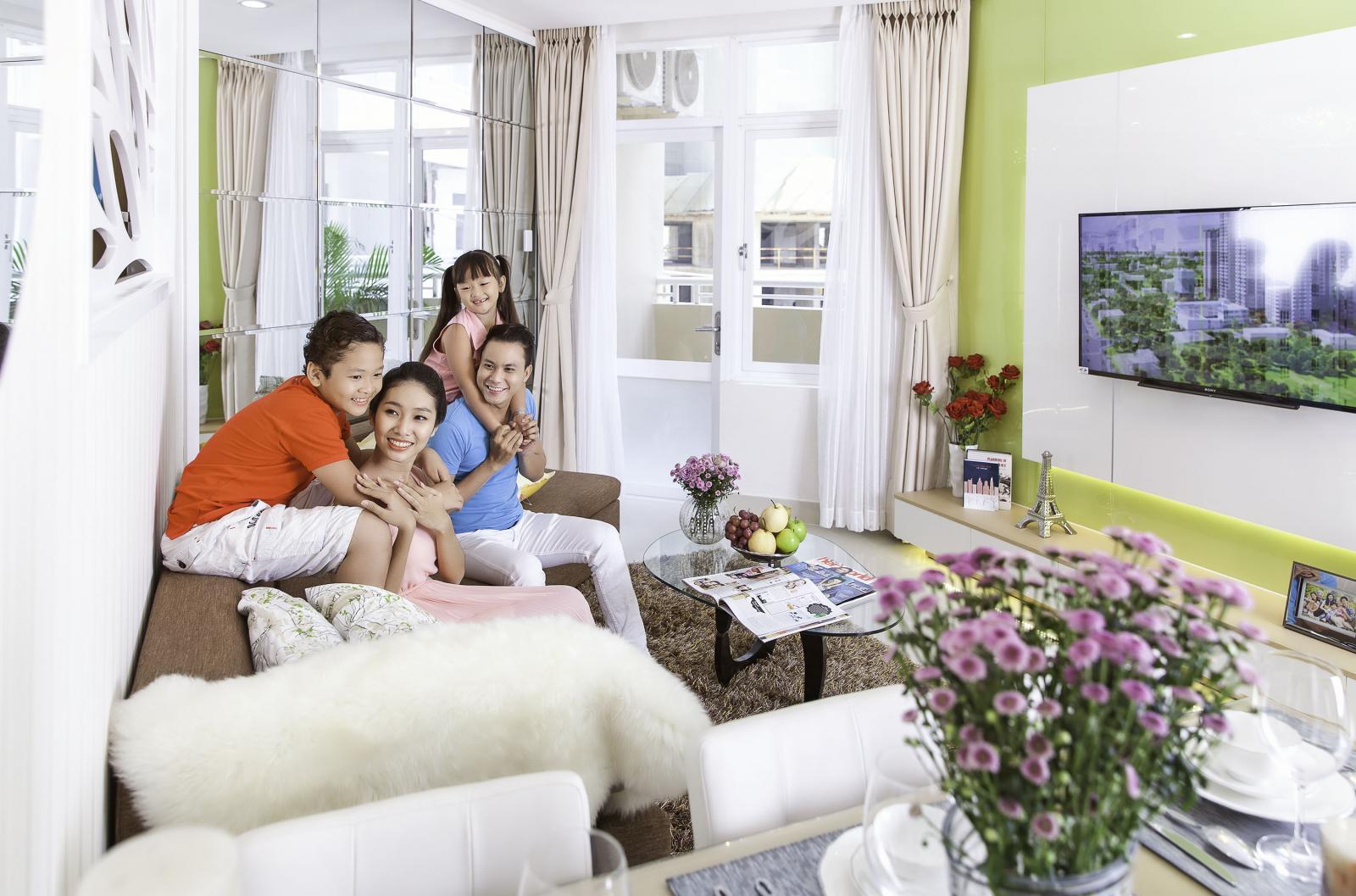 gia đình 4 thành viên đang ngồi trên sofa trong phòng khách căn hộ