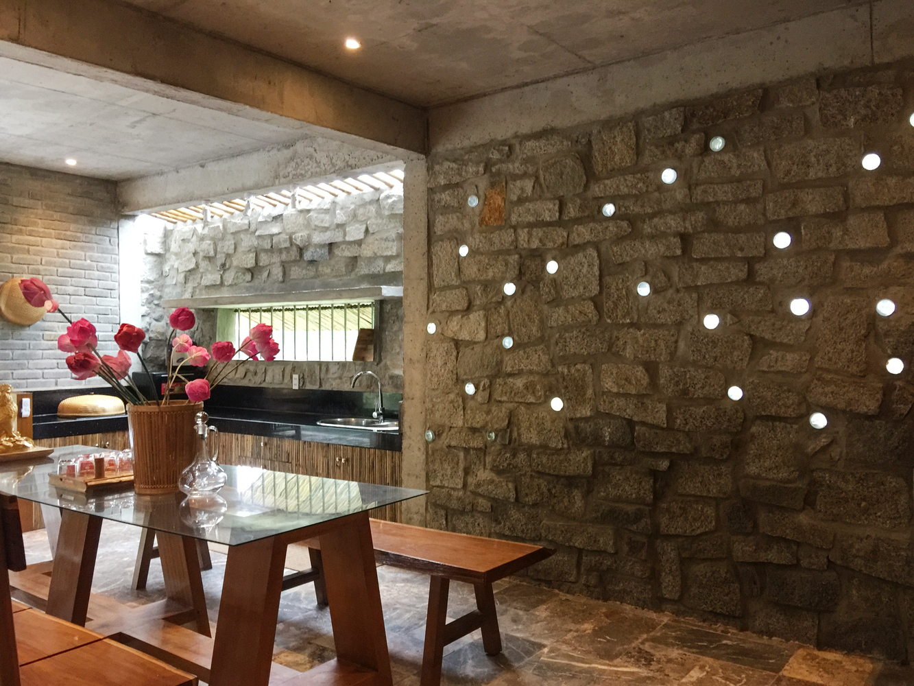 Không gian bếp có bàn ăn và lọ hoa sen trang trí