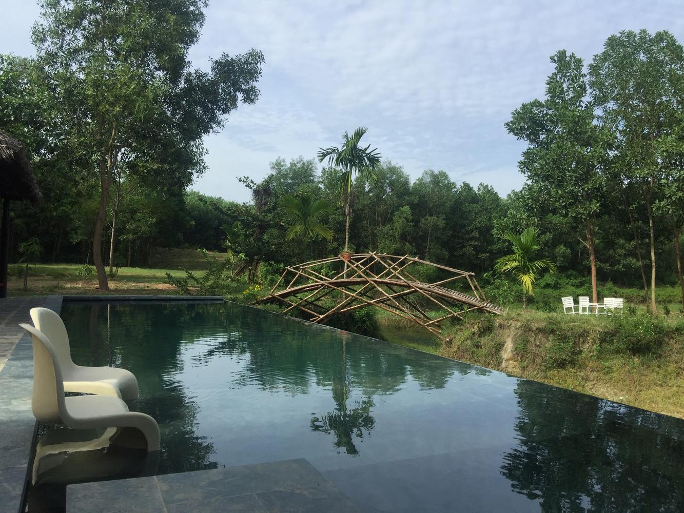 Cầu tre và hồ nước nhìn từ bể bơi của ngôi nhà trang trại