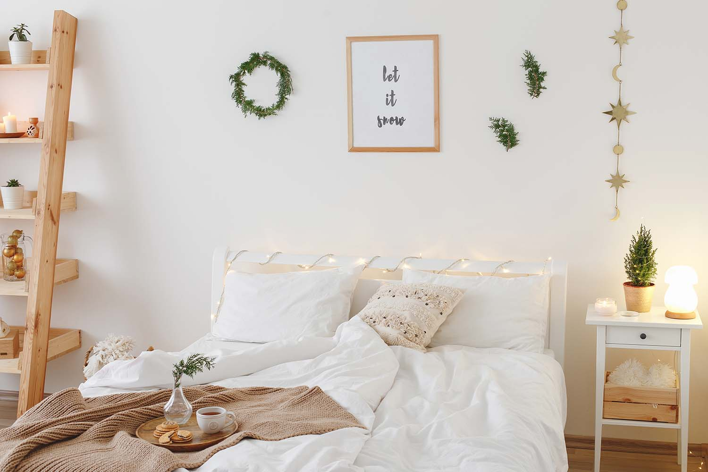 Phòng ngủ nhỏ có giường, đệm, kệ, cây trang trí