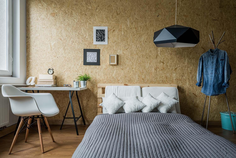 Phòng ngủ có giường, bàn ghế, tranh ảnh trang trí trên tường