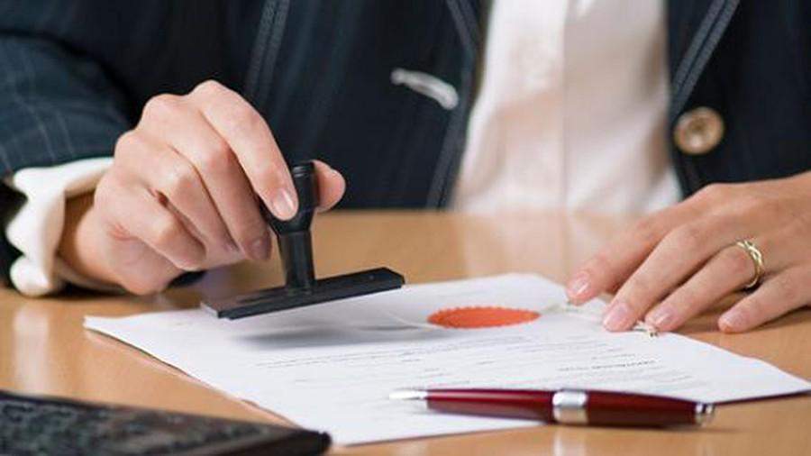 Bàn tay cầm con dấu làm thủ tục công chứng hợp đồng mua, bán nhà đất