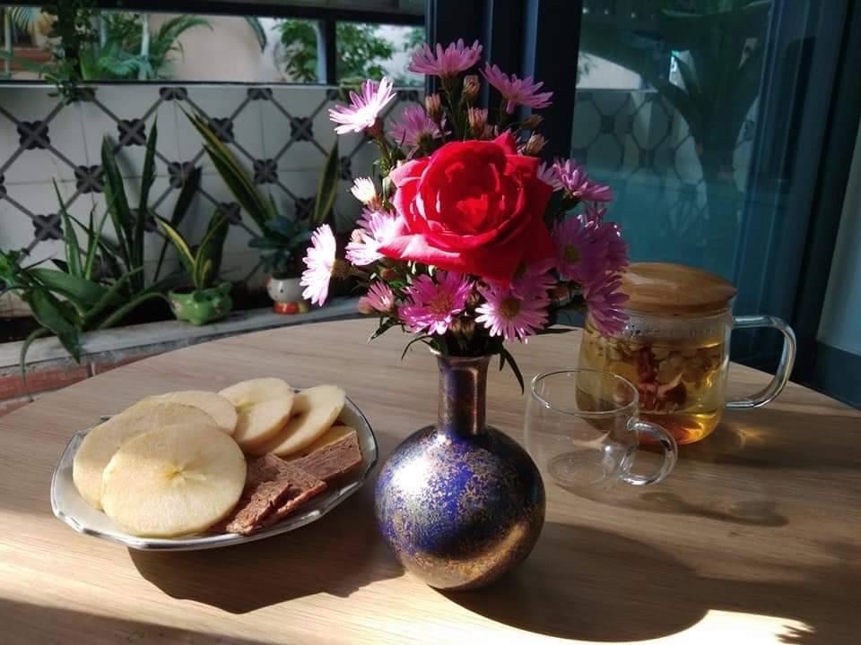 Cốc trà và bình hoa, quả trên bàn, phía sau là cảnh sân vườn