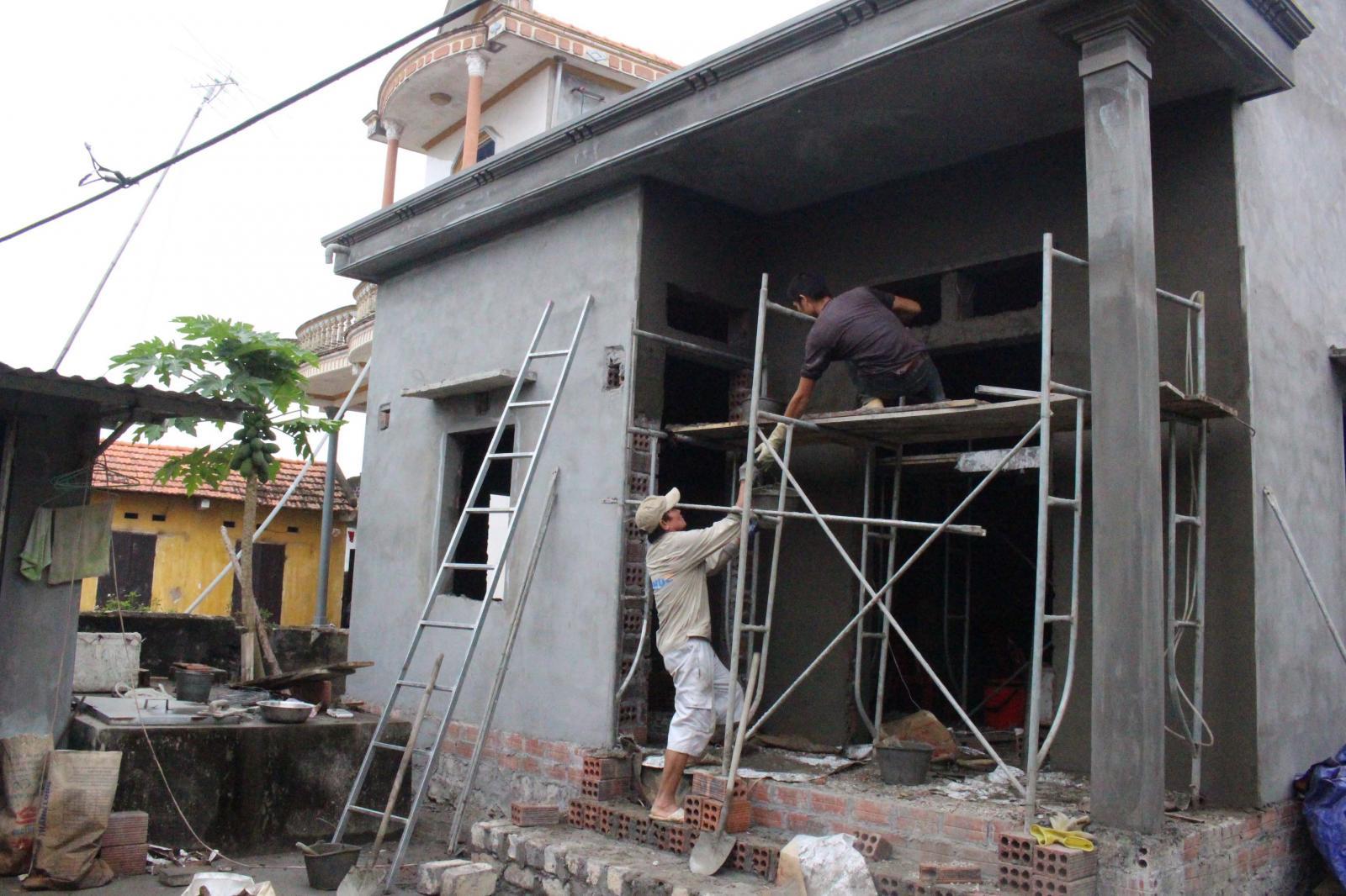 hai người đàn ông đang xây nhà