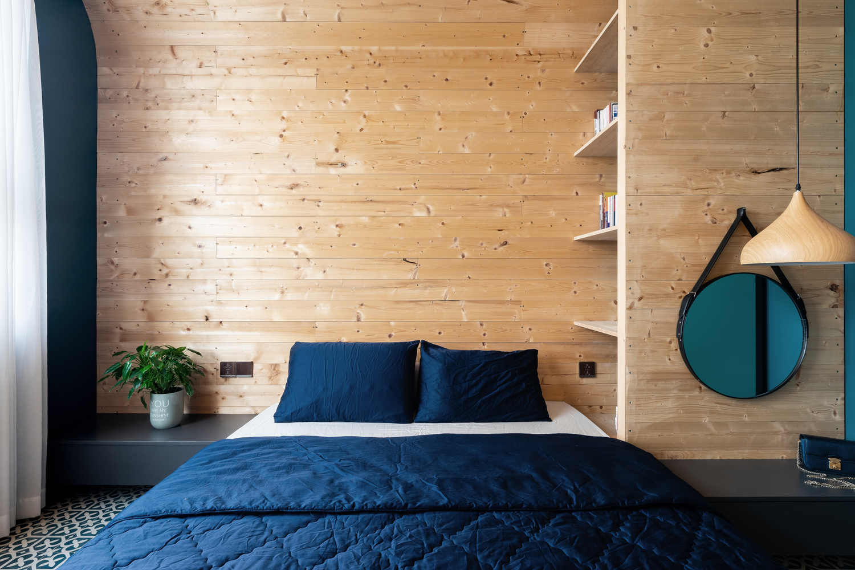 Phòng ngủ thoáng đãng, đầy ánh sáng tự nhiên, hài hòa với vẻ mộc mạc của hệ khung mái vòm bằng gỗ.