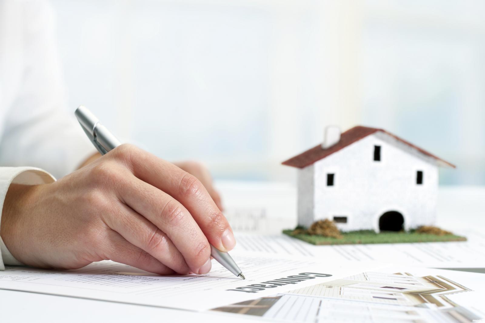 một người đang viết hợp đồng mua bán nhà đất bằng giấy tay