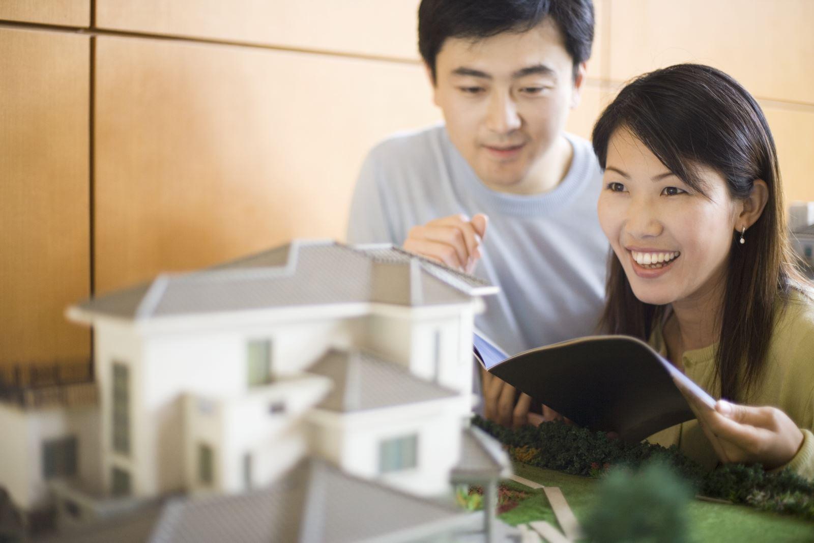 một cặp vợ chồng đang quan sát mô hình ngôi nhà