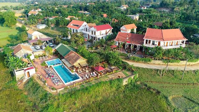 khu du lịch farmstay nhìn từ trên cao có nhiều công trình nhà ở, hồ bơi và cây cối